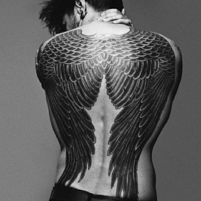 ein mann mit einem tollen, märchenhaften, schwarzen engel tattoo - hier sind zwei schwarze engelsflügel mit langen schwarzen federn