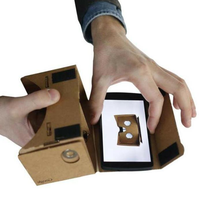 hier sind hände. selbt gemachte virtuelle brille aus pappe - idee für vr brille