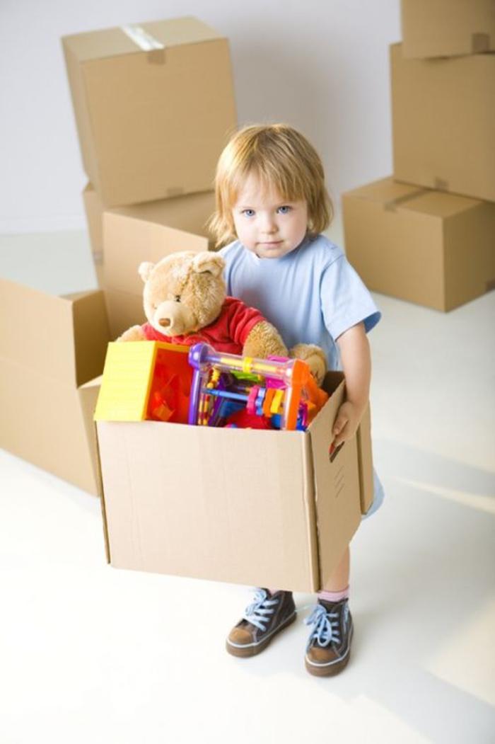 Spielzeuge einpacken, süßes Kind, in neues Haus umziehen, Umzugskartons