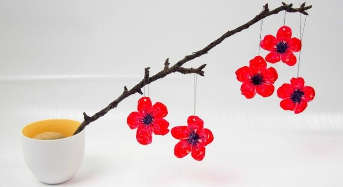 diy deko für zuhause selber machen, blumentopf, ast, rote blumen aus plastik