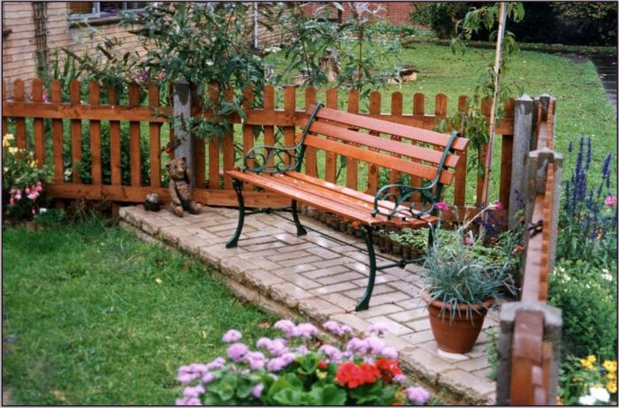 eine Bank Sitzecke im Garten - grüner Rasen viele bunte Blumen Garten pflegeleicht