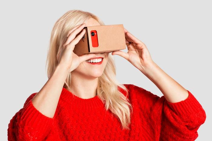 hier ist eine lächelnde frau mit einem schönen roten pullover - vr brille aus pappe und ein rotes handy