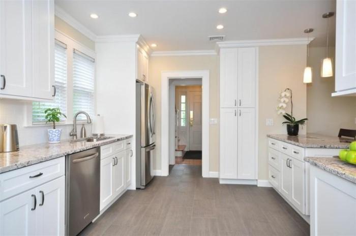 Küche in cremeweiß. offene Küche ohne Trennwand, weiße Schränke mit schwarzen Griffen