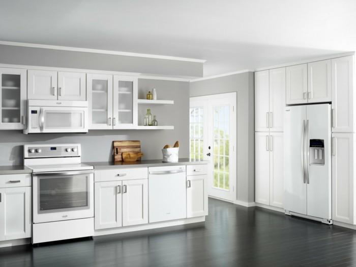 moderne offene Küche in L-Form, graue Küchenwand, schwarzer Holzboden, weißer Kühlschrank mit Eiswürfelbereiter