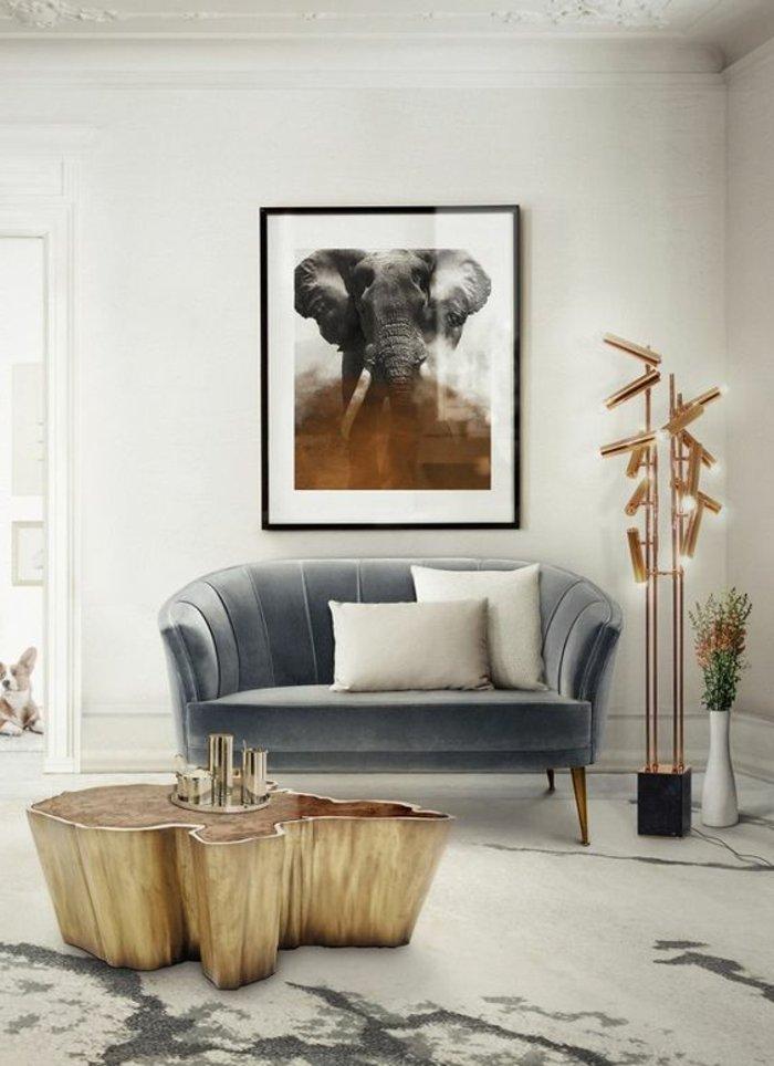 graues Zimmer mit einem grauen Sofa viele Lampen und Tisch aus Treibholz
