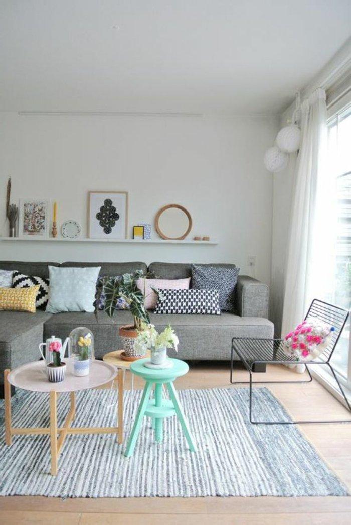 viele kleine Möbel voller Vasen und Blumentöpfe in einem grauen Zimmer