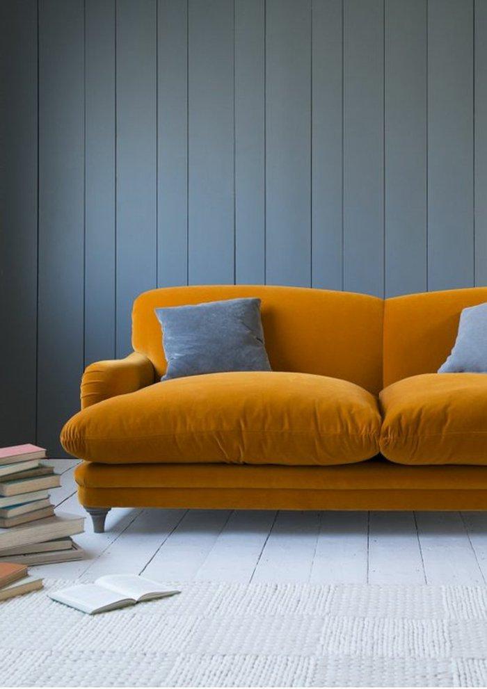 gelbes Sofa mit grauen Kissen, graue Bodenbeläge und graue Wände - graues Zimmer