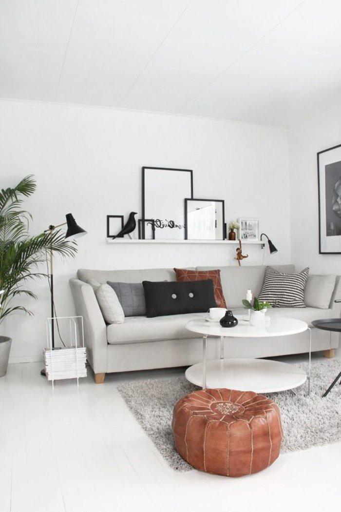 graues Zimmer, runder, weißer Tisch, Bilderleiste schön dekoriert, graues Sofa