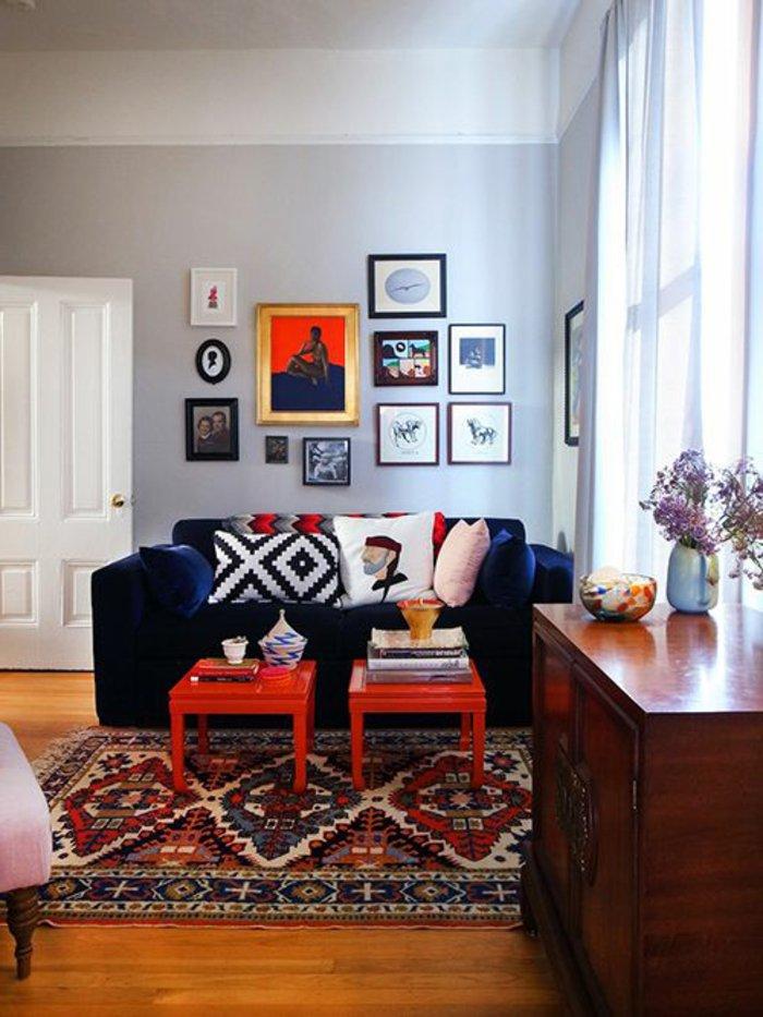 graues Zimmer mit viele Wandbilder, bunte Kissen, blaues Sofa, Regal aus Holz