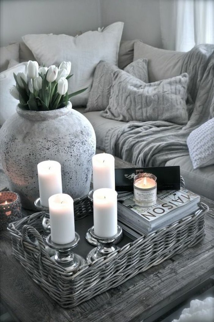 graues Zimmer in Beton Optik mit Vase voller weiße Tulpen und vier Kerzen