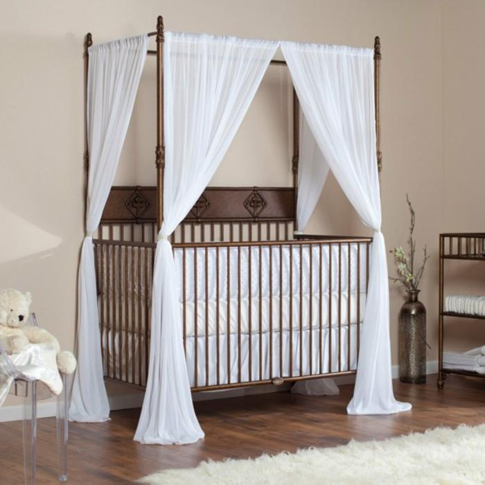 Holzbett mit weißem Himmel, Bio-Holz, Kuschelbär auf Stuhl, Babyzimmer in Pastelltönen