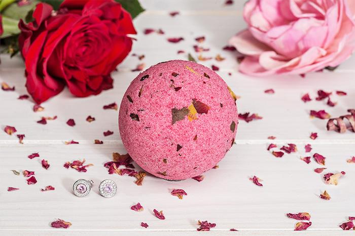 rote rose, getrocknete roseblätter, silberne ohrringe mit kristallen
