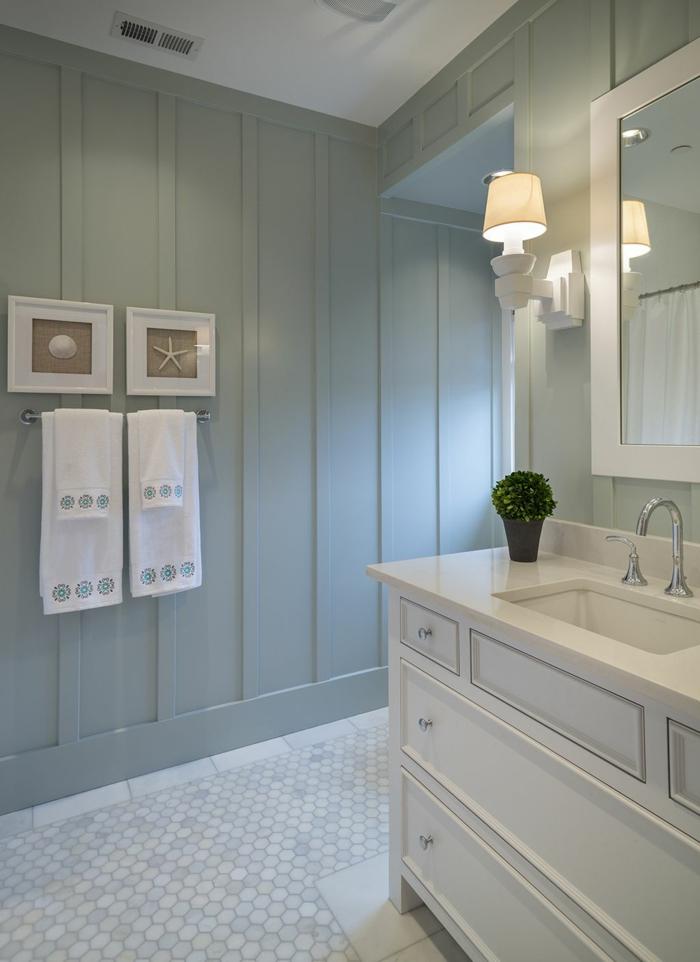maritime Badezimmer, blass blaue Wand mit Bilder von Muschel und Seestern, weißer Waschbecken mit Schränken, weiße Handtücher,