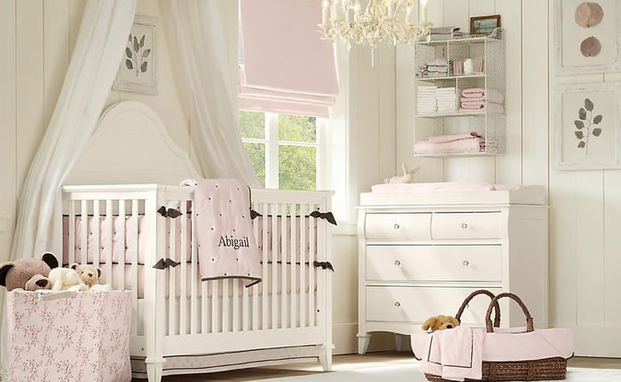 Babyzimmer in Shabby Chic, weiße Holzmöbel, hellrosa Bettwäsche, verspielter Kronleuchter