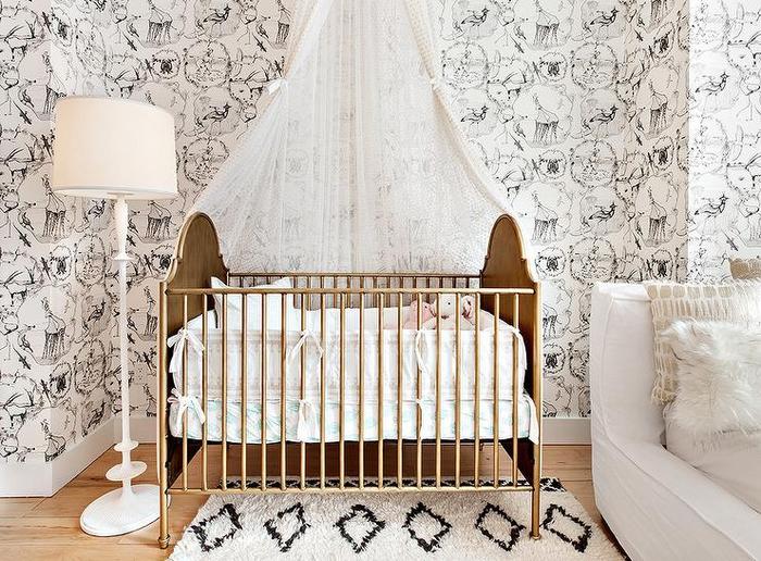 Babyzimmer in Weiß, Babybett mit Himmel, weiße Stehlampe, kleine Kuscheltiere im Bett