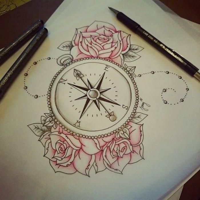 blatt papier und drei schöne pinke rosen und eine idee für einen compass tattoo