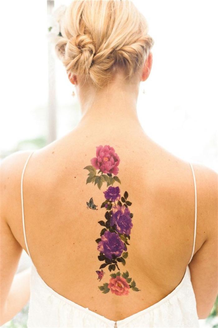 Rücken Tattoo für Frauen, Blumen-Motive in Rosa und Lila, kleiner Schmetterling