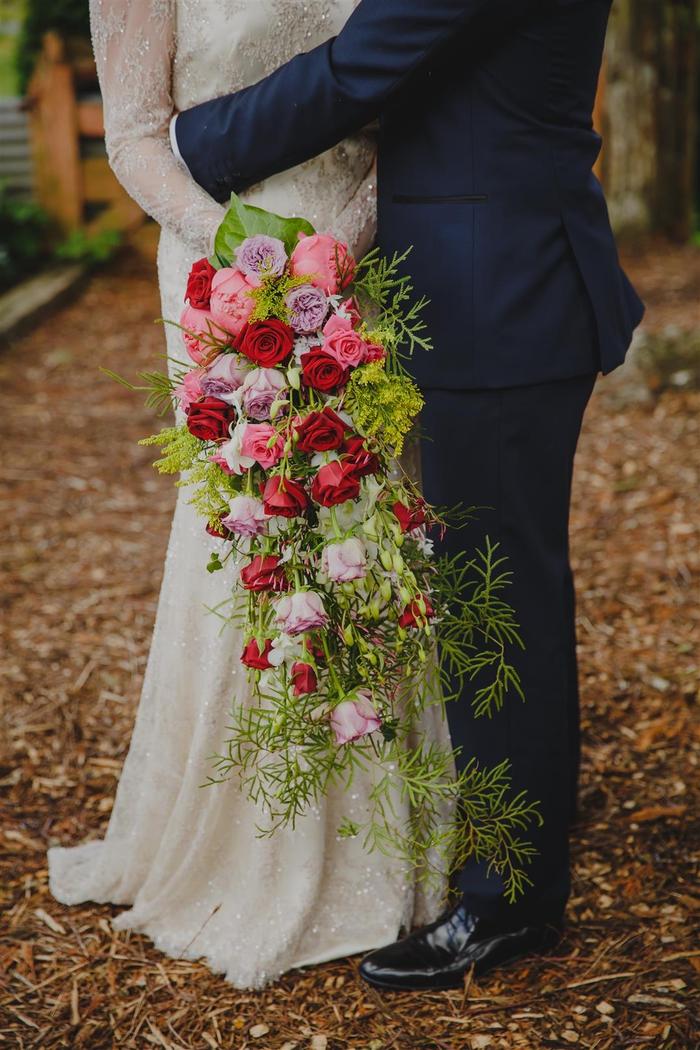 Hochzeitsstrauß vintage länglicher Strauß mit roten und lila Rosen und viele grüne Pflanzen