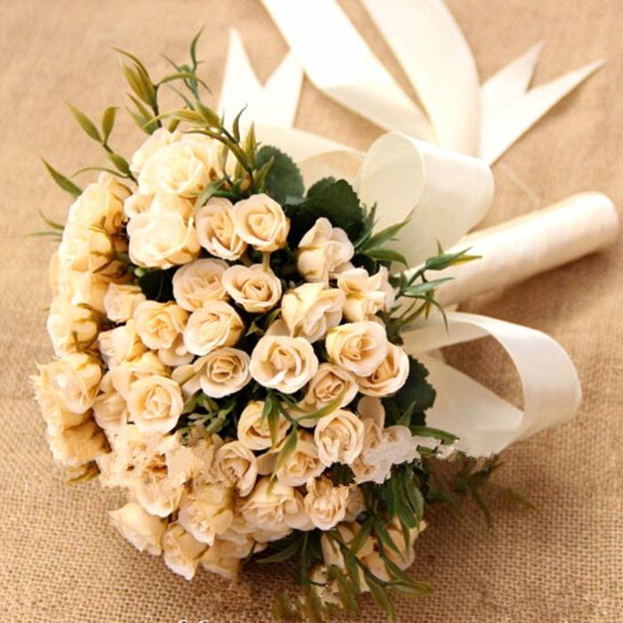 kleine orange Rosen und ihre grünen Blätter ein weißes Band Hochzeitsstrauß vintage
