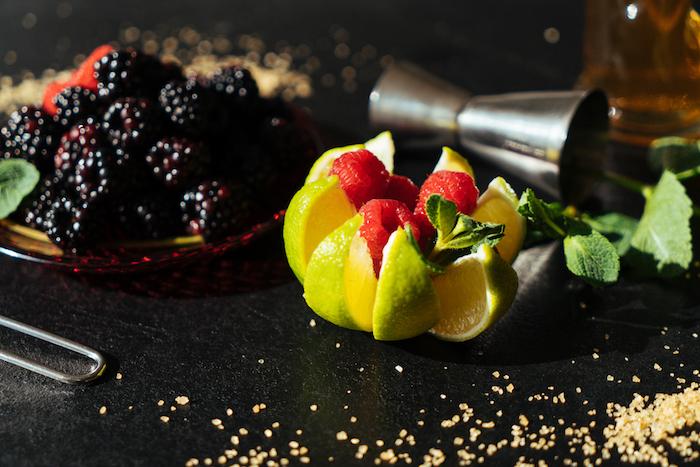 Zutaten für fruchtigen Cocktail, frische Brombeeren und Himbeeren, Minzblätter und Limettenstücke