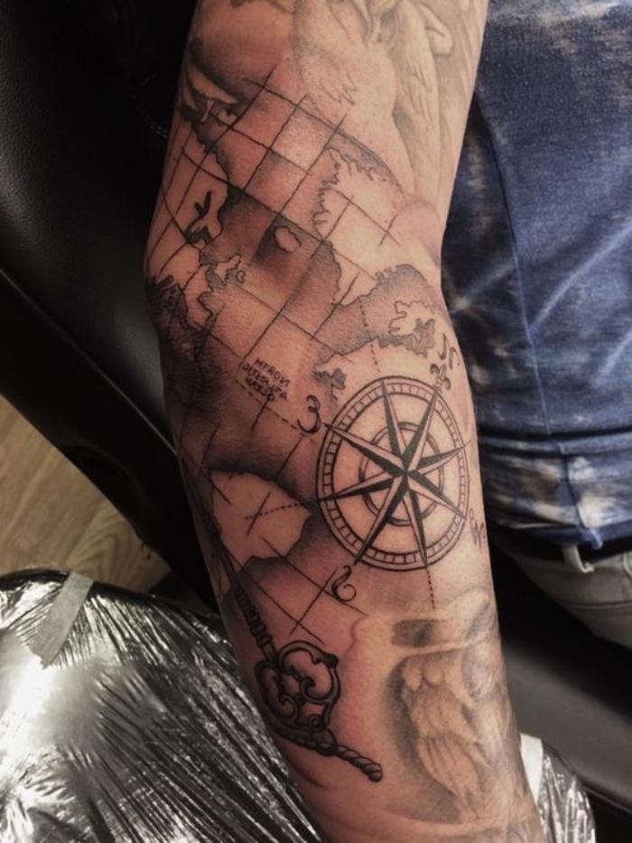 die welt und eun großer kompass - idee für einen sehr schönen compass tattoo auf der hand