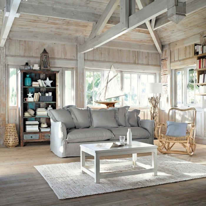 Wohnzimmer maritimer Stil, großes Couch in grau, Schaukelstuhl mit blauem Kissen, großes Segelboot Dekoration