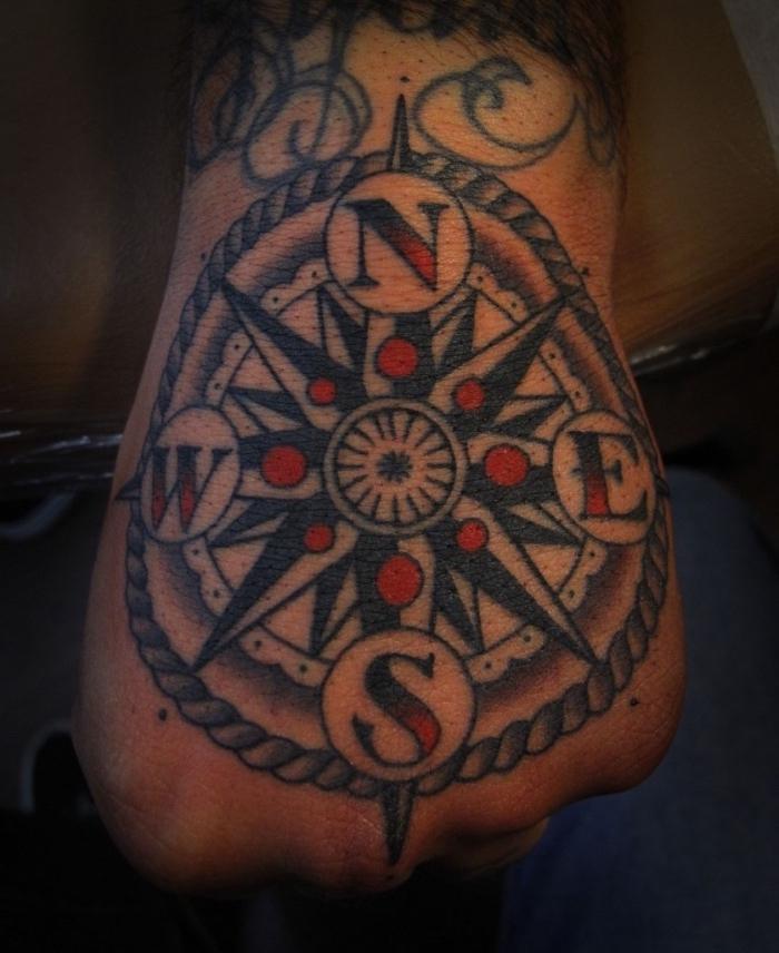 hier ist noch eine idee für einen großen schwarzen tattoo auf der hand - ein tattoo mit kompass und roten punkten