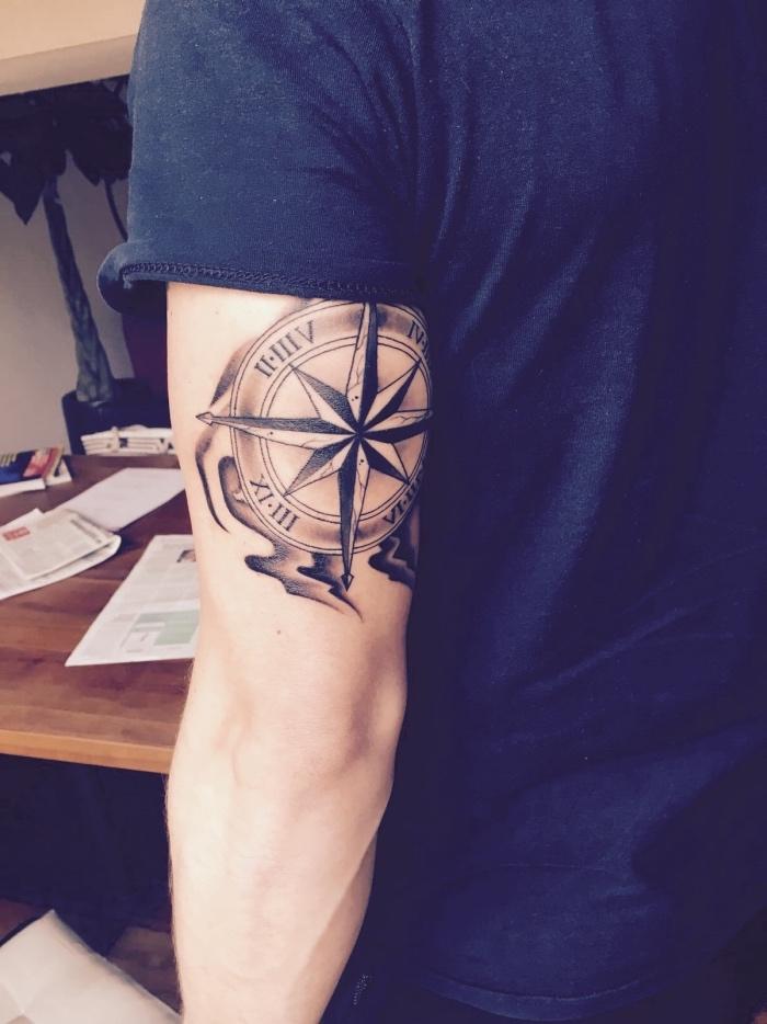 hier ist ein mann mit einem großen schwarzen compass tattoo auf seiner hand - idee für tätowierung mit kompass für männer