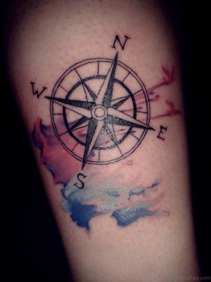 eine idee für einen tattoo mit einem großen schwarzen kompass auf der hand mit einigen bunten farben