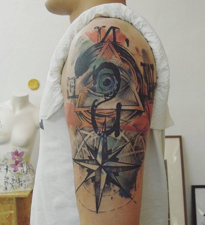 ein mann mit einem verrückten bunten tattoo auf dem schulter mit einem großen blauen auge und einem großen schwarzen kompass
