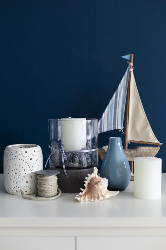 Deko maritim Wohnzimmer, dunkelblaue Wand, weiße Kommode, kleines Segelboot und Stachelschnecke, blaue Vase,