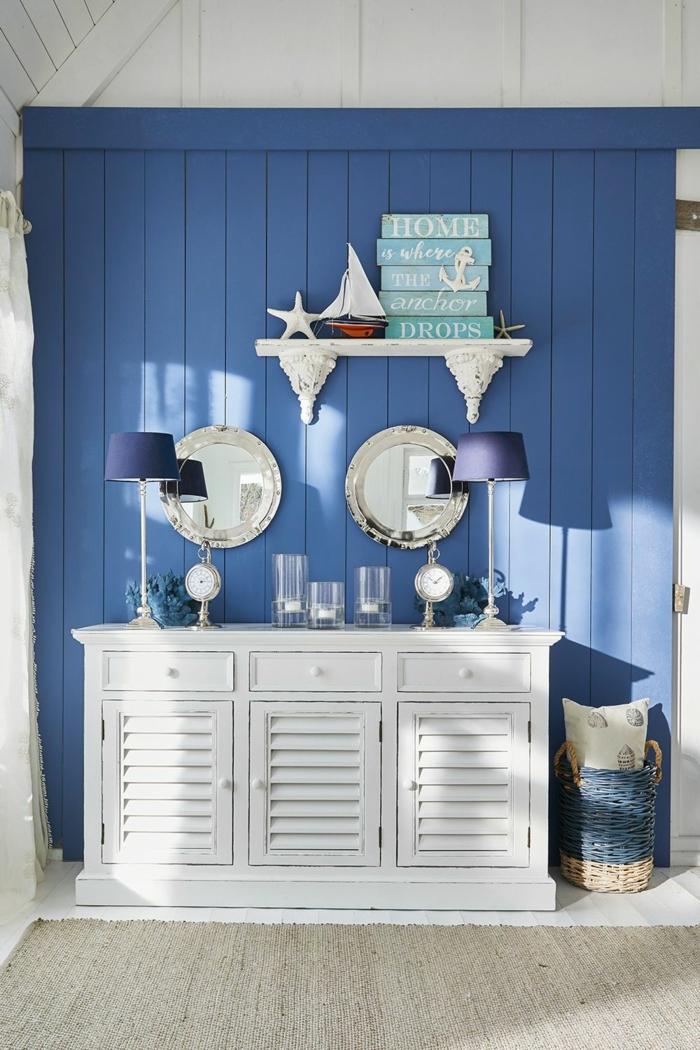 Maritime Einrichtung, weiße Kommode mit blauen Lampen obendrauf, blau gefärbte Wand, Seestern und Segelboot Dekoration