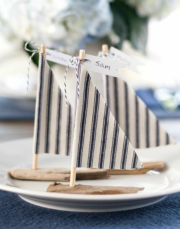 Maritime Deko selber machen für Party, Segelboot aus Treibholz mit Fahne in blau und weiß, drei Boote auf einem Teller