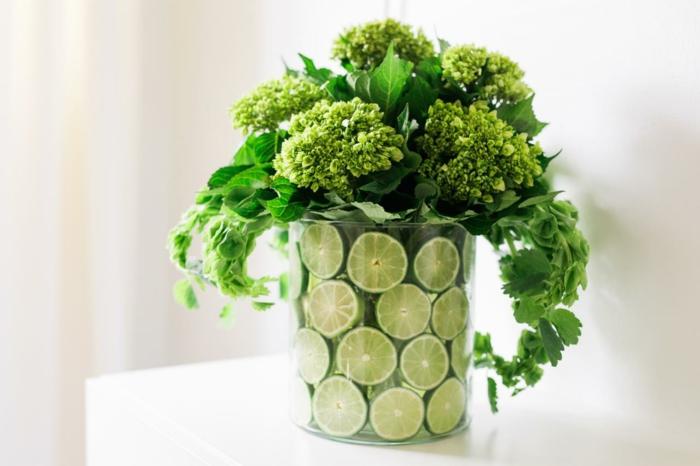 diy tischdekoration, vase mit limettenscheiben und grünen blumen