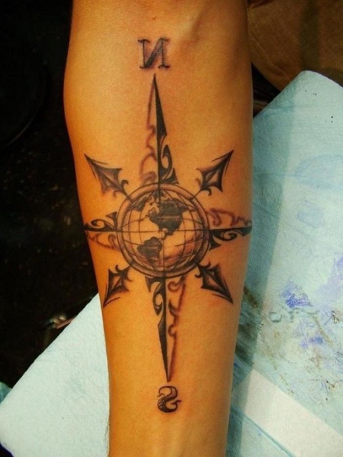 schwarzer kompass, der planet, erde - eine unserer ideen für einen compass tattoo auf der hand
