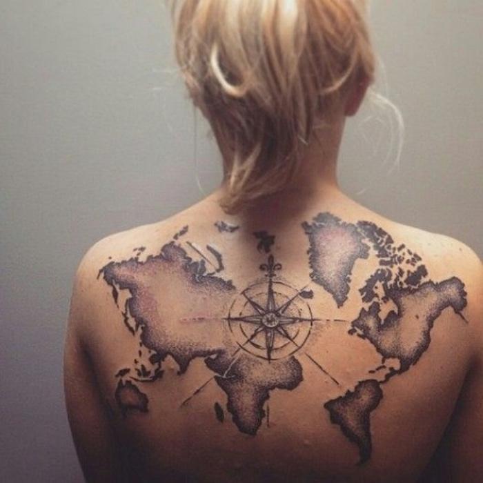ein schwarzer kompass und die karte der welt - eine idee für einen modernen tattoo auf dem rücken einer jungen frau