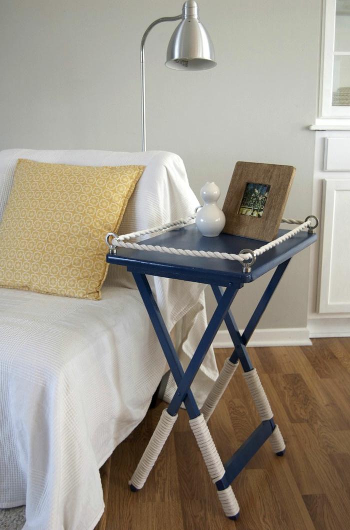 Moderne Inneneinrichtung im maritimen Stil, kleiner blauer Tisch mit Seil, maritime Möbel, gelber Kissen