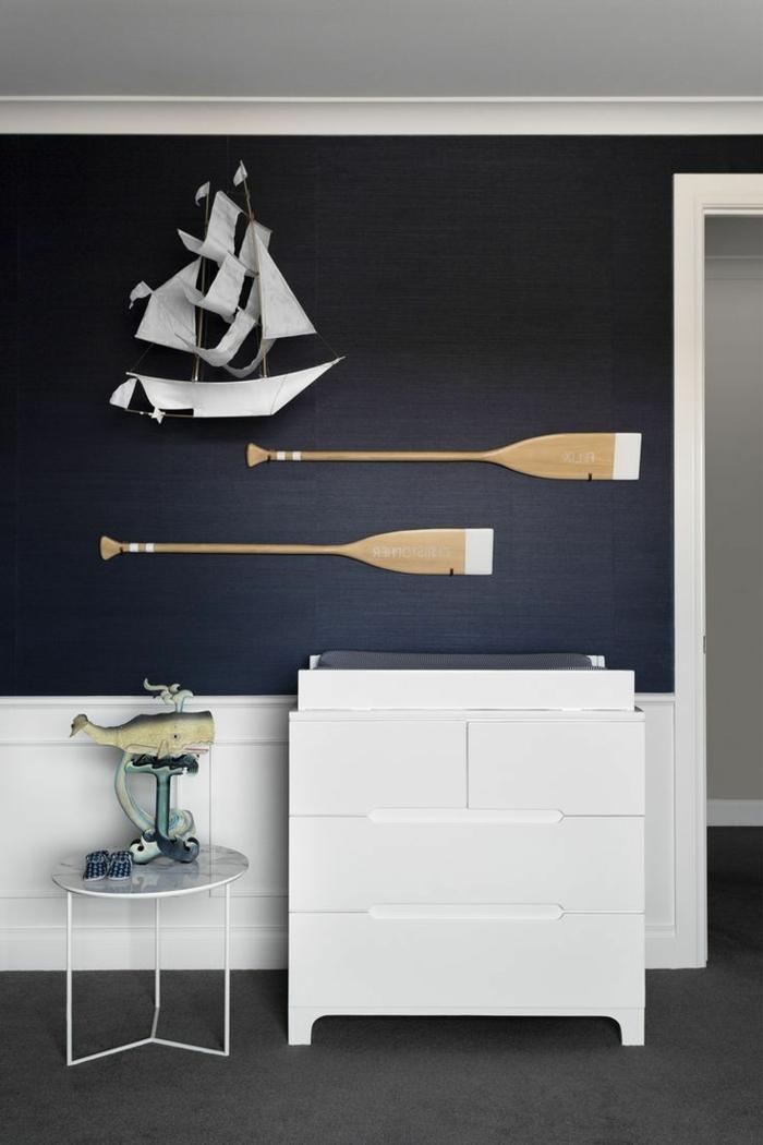 Dunkelblaue Wand mit aufgehängtes Segelboot und zwei Ruder, weiße Kommode, maritime Farben und deko Figuren