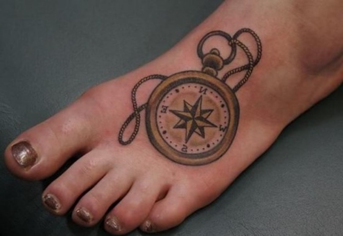 hier finden sie eine idee für einen tattoo auf bein - ein bein mit nagellack und einer tätowierung mit einem goldenen kompass