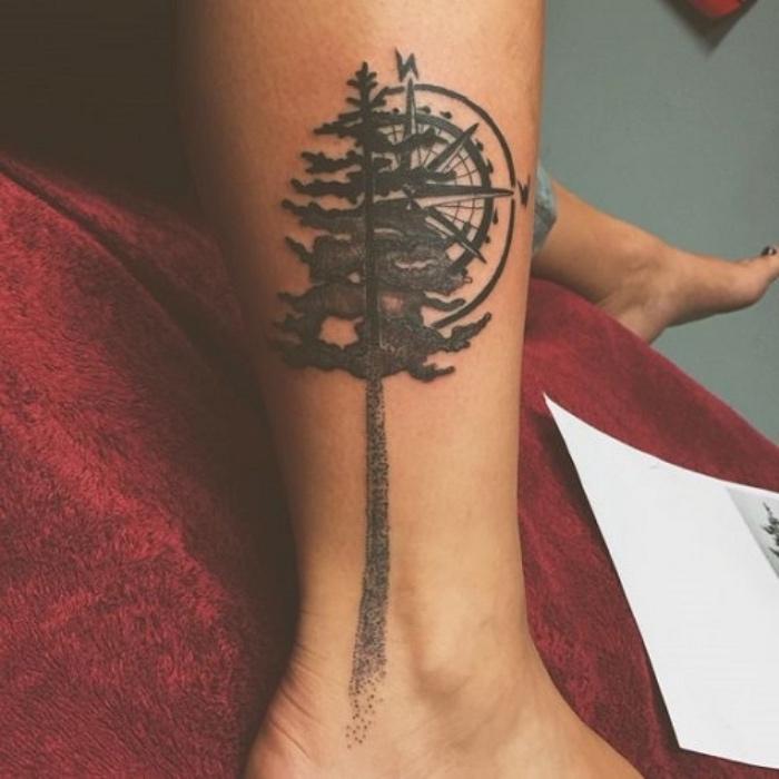 das ist eine unseret tollen ideen für einen schwarzen tattoo mit einem langen, großen, schwarzen baum und einem großen schwarzen kompass - idee für eine tätowierung auf bein