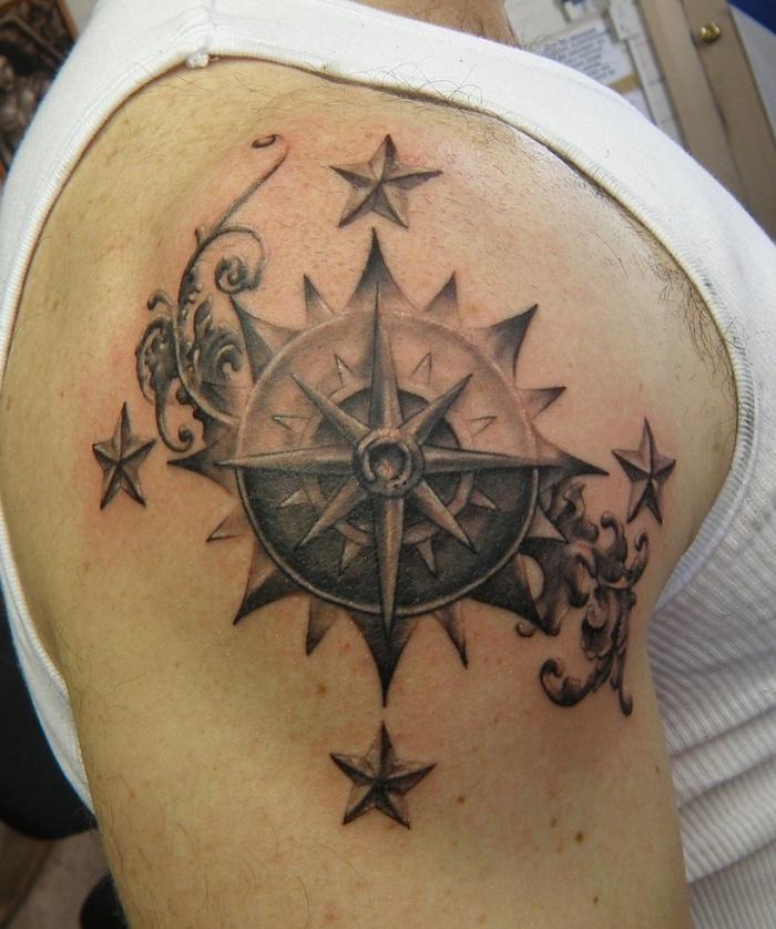 eine compass tätowierung auf dem schulter mit vier sternen - ein compass tattoo für mann