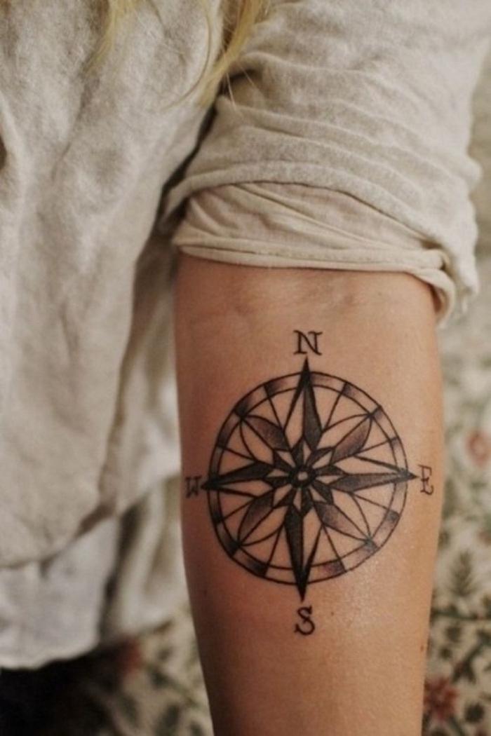 eine frau mit einer schwarzen kleinen tätowierung mit einem schwarzen kompass - idee für einen tattoo auf hand