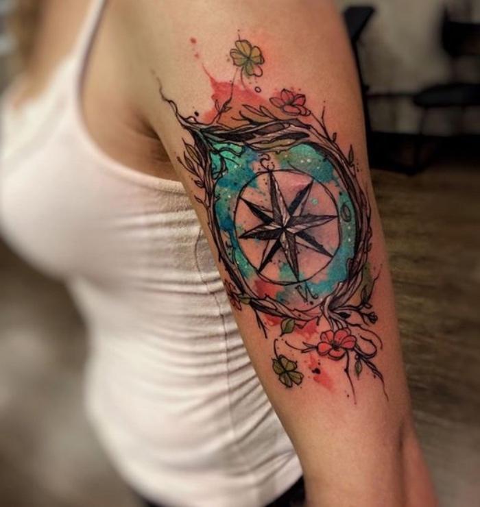 hier finden sie eine junge frau mit einer märchenhaften, großen und schönen tattoo mit einem schwarzen, großen kompass mit zwei roten blumen und zwei grünen blumen