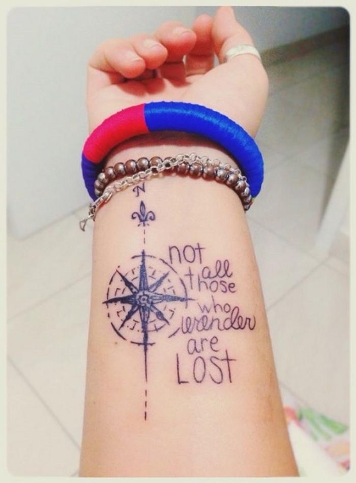 eine hand einer frau mit einem ring und mit einem schwarzen tattoo mit einem kompass mit schwarzen überschriften