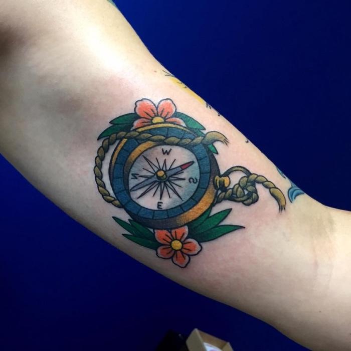 her zeigen wir ihnen eine idee für einen tattoo mit einem kleinen kompass mit zwei roten blumen und kleinen grünen blättern - eine märchenhafte tätowierung auf der hand