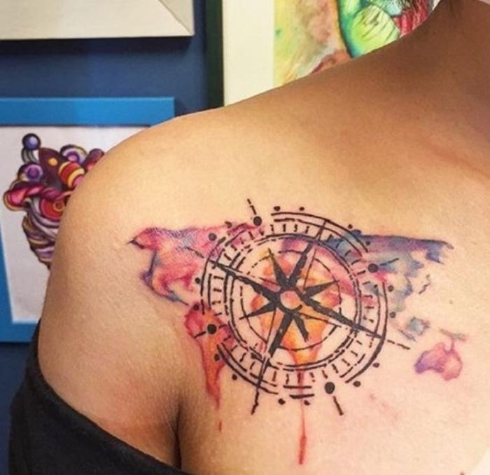 eine bunte weltkarte und ein großer schwarzer kompass - idee für einen compass tattoo auf dem schulter