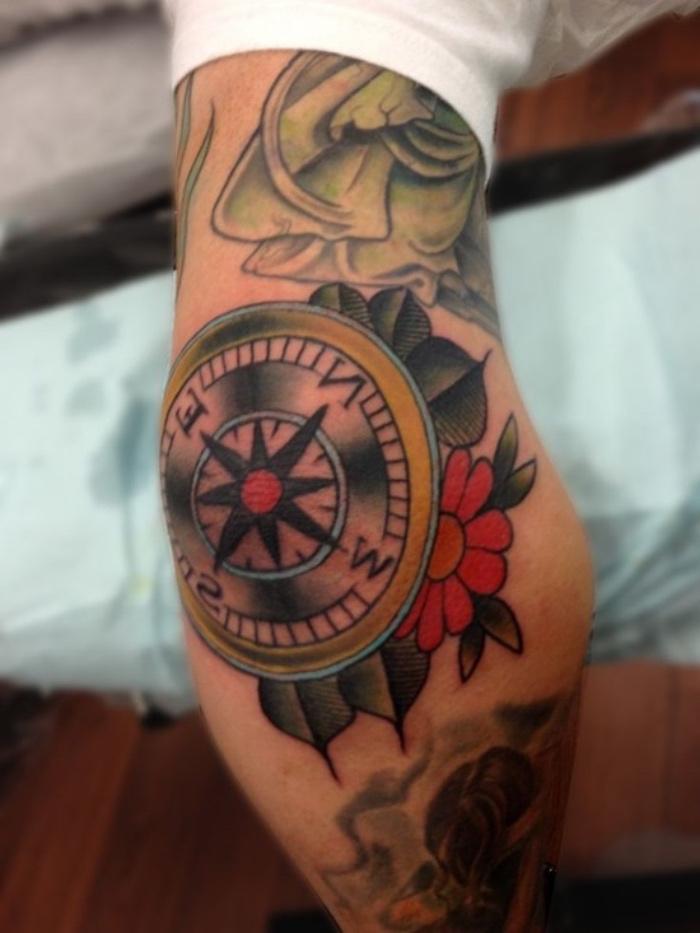 ein kompass mit einer roten blume und grünen blöttern - idee für einen märchenhaften compass tattoo auf einer hand