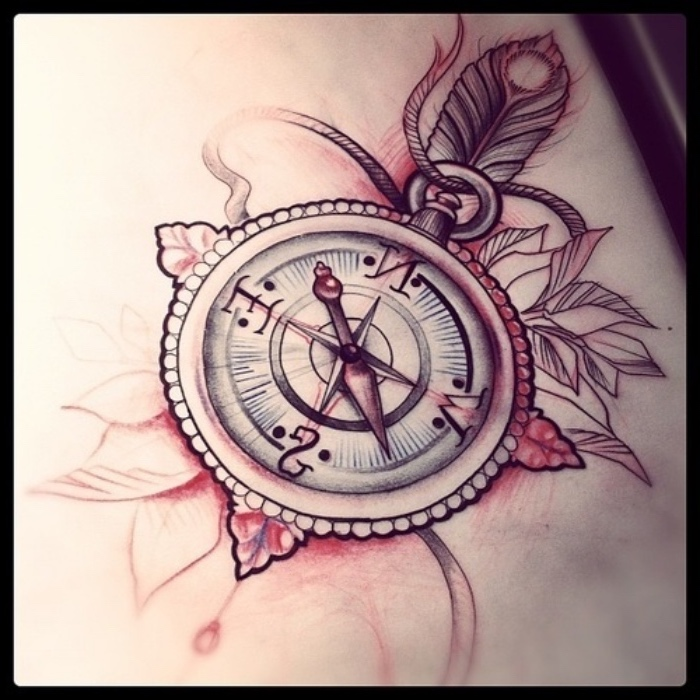 hier ist eun roter tattoo mit einem großen kompass mit einer kleinen vogelfeder und weißen blättern und kleinen roten blumen