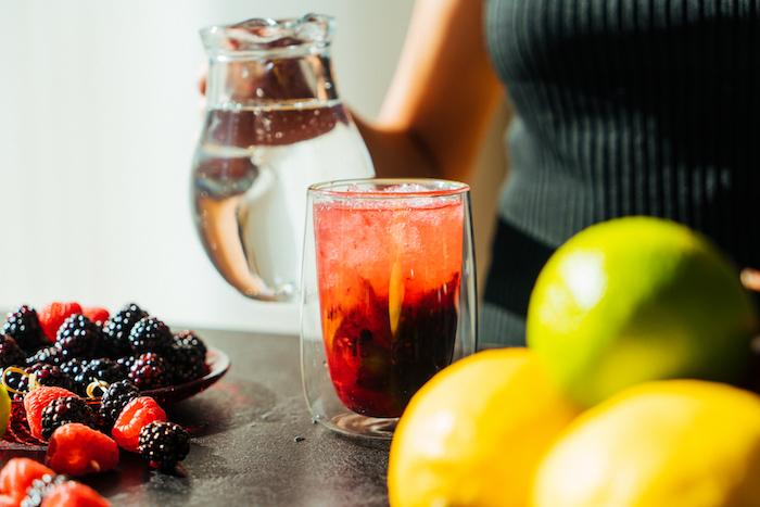 Mit zerstoßenem Eis und Sodawasser auffüllen, Cocktail mit frischen Beeren