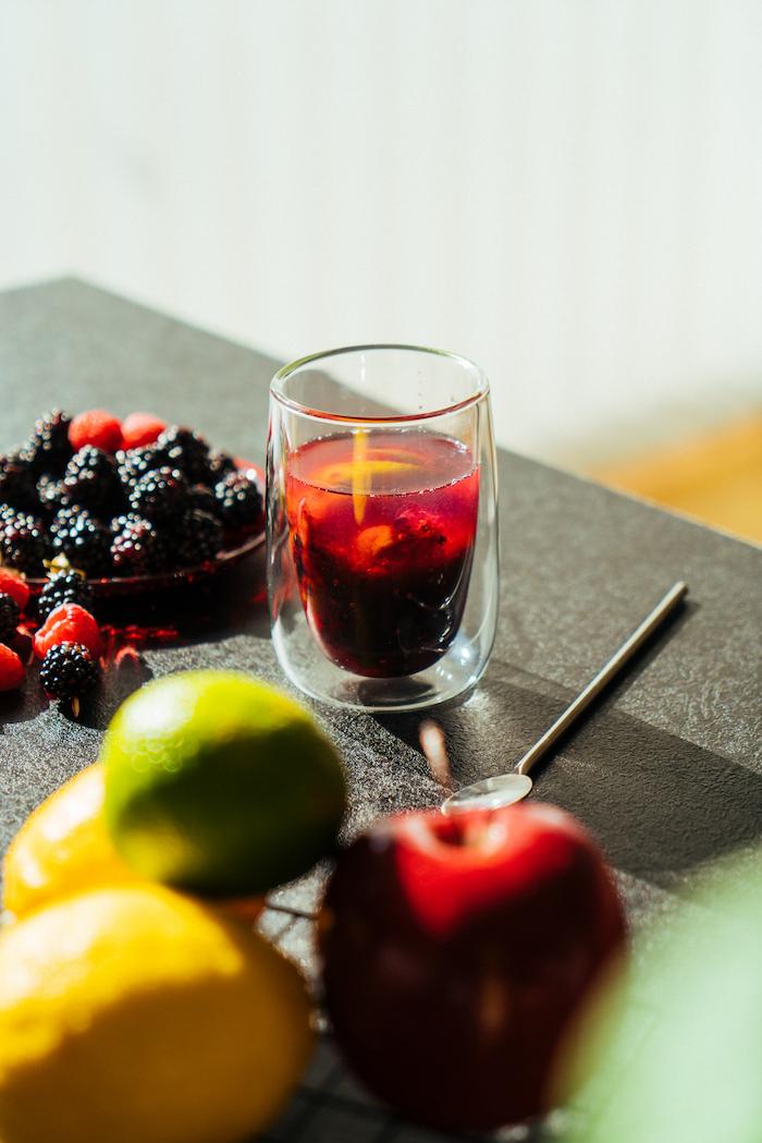 Limette und frische Beeren mit einem Mörser zerdrücken, Sodawasser dazugießen